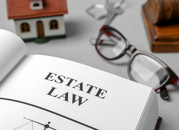 Estate law book with glasses and a house on the background