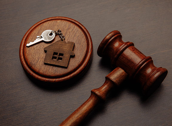 A gavel with a house's key next to it